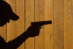 Shadow of a man with a gun on a wooden fence. With space for text or image Stock Photos