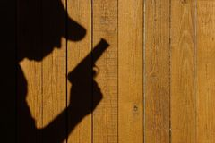 Shadow of a man with a gun on a wooden fence. With space for text or image Stock Images