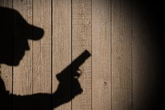Shadow of a man with a gun. On a wooden fence, with space for text or image Stock Image