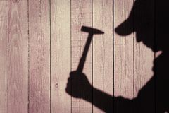 Shadow of a man with hammer on natural wooden background Royalty Free Stock Photos
