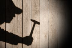 Shadow of a man with hammer on natural wooden background Royalty Free Stock Photo