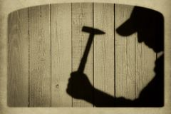 Shadow of a man with hammer on natural wooden background Stock Photo