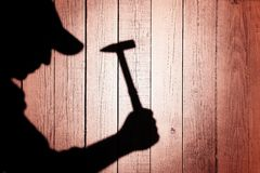 Shadow of a man with hammer on natural wooden background Stock Image