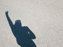 Shadow of a man with his arm up waving. Shadow of man in the road stock photo