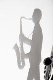 Shadow of man holding saxophone. Dark shadow of man holding saxophone Royalty Free Stock Images