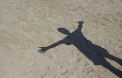 Shadow of man with open arms on sand background. Shadow of man with open arms on sand background in Cunda / Turkey Royalty Free Stock Images