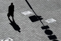 Shadow of the man on pavement Stock Images