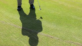 Shadow of a man playing golf. The shadow of a man playing golf on the grass. Ultra HD video stock footage