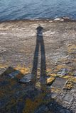 Shadow man in a sea shore rock royalty free stock images
