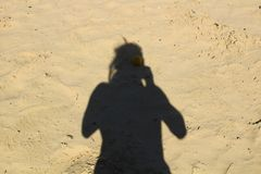 Shadow of man. On the sand at the lake beach Stock Photos