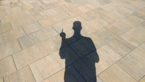 The shadow of a man showing an obscene gesture