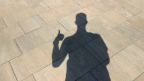 The shadow of a man shows gesture cool