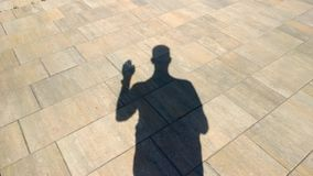 The shadow of a man shows gesture. Hello stock video footage
