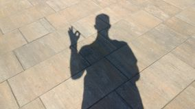 The shadow of a man shows gesture ok