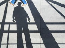 Shadow of a man on the sidewalk. Among the beams, visible someone`s feet Stock Image