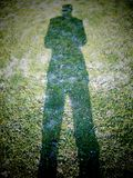 Shadow man. Shadow of the man standing on the grass Stock Photography
