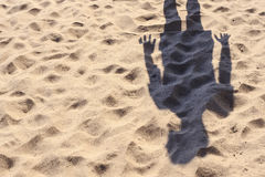 Shadow of a man standing on a yellow sand beach on a sunny day. Royalty Free Stock Images