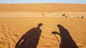 Shadow of a man and woman`s photography travel in the desert. royalty free stock photography