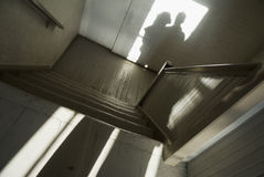 Shadow of man and woman in stairwell Stock Photos