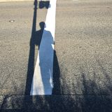 Shadow of a men on traffic. Shadow of man waiting to cross the road Royalty Free Stock Photo