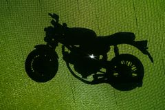 Shadow of motorcycle. On green ground in backlight stock image