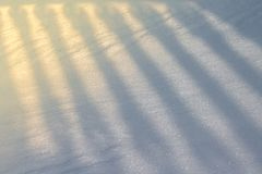 Shadow from an openwork fence, falling on the snow as a background or a backdrop.  Stock Images