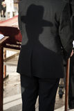 Orthodox Shadow. A shadow of an orthodox Jewish man casted on the back side of the suit of the orthodox Jewish man standing in front of him. Shot in the Wailing Royalty Free Stock Images
