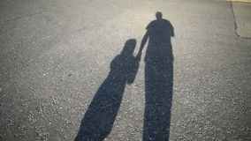 Shadow of parent and child walking along road together stock footage