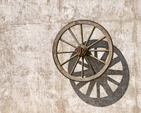Wooden Wagon Wheel. An old wooden wagon wheel casts a shadow on a concrete wall Royalty Free Stock Image