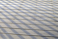 Shadow patterns on snowy deck on winter day. A light dusting of snow fell on a wooden deck during the day. By sunset, shadows from the posts revealed a pattern Stock Photography