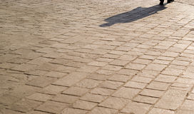 Shadow on a pavemet road. A shadow of a man in a pavement road in Italy Stock Photo