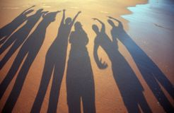Shadow people. Shadows of some people posing at the seashore Royalty Free Stock Photo