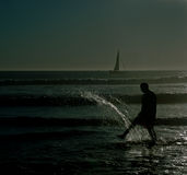 Shadow people beach kicking water royalty free stock photo