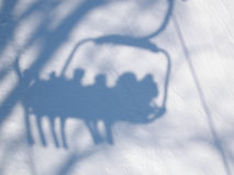 Shadow of people with skis on the lift in the mountains. People on the lift in the mountains Royalty Free Stock Image