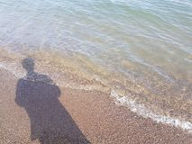 Shadow of a Person Casted on the Beach and Tide Royalty Free Stock Image