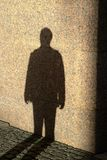 Shadow of person on the stone wall at sunset time Stock Photography