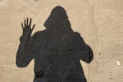 The shadow of the photographer in the hood on the pavement. silhouette on the ground royalty free stock photography