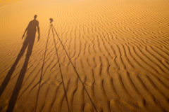 Shadow of a photographer standing next to his tripod Stock Image