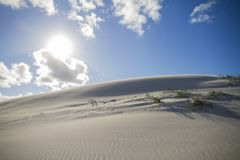 Shadow play on a sand dune with backlight effect and the sun shining in the blue sky with white clouds royalty free stock photography