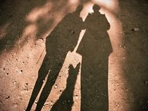 Shadow play on the sandy ground of two humans and a dog. Large and clear shadow on the sandy ground floor of two adult humans and in between a small dog sitting royalty free stock photos