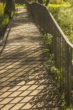 Footbridge. The shadow of the railing on an old wooden footbridge Stock Photos