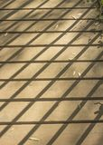Shadow on footbridge. The shadow of the railing on an old wooden footbridge Royalty Free Stock Photo