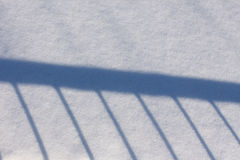 Shadow of railing on the snow Stock Images