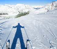 A shadow of ready to go downhill skier. On empty fresh-made ski slope and mountains panorama on a background Stock Photos
