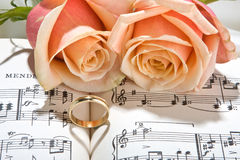 Shadow of rings. Sheet music of the Wedding March with roses and rings royalty free stock images