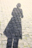 Shadow on the road. Shadow of person on old stone road Royalty Free Stock Photo