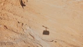 Shadow of a ropeway cabin rising in Masada desert. Aerial cable car going up on a sunny day. Sand and rocks. Israel 4K. Shadow of a ropeway cabin rising in stock video