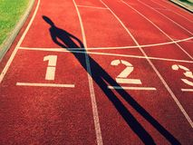 Shadow of runner. White track number on red rubber racetrack, texture of running racetracks Stock Images