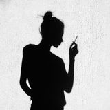 Shadow of sad girl smoking around on wall background Stock Photo