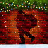 Shadow of Santa on a brick wall. Christmas background with Shadow of Santa, fir tree branches and light bulbs on a brick wall, illustration Royalty Free Stock Image